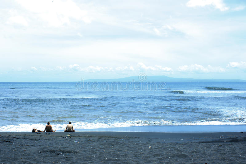 One day on the ocean and beach with black sand. Sea, sun, sky, beach and clouds. Relax on the ocean. It can be used to illustrate about travel, nature, ocean royalty free stock photos