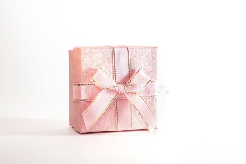 One decorative holiday gift box with ribbon bow for congratulations, surprise, pink present on white background with copy space royalty free stock photos