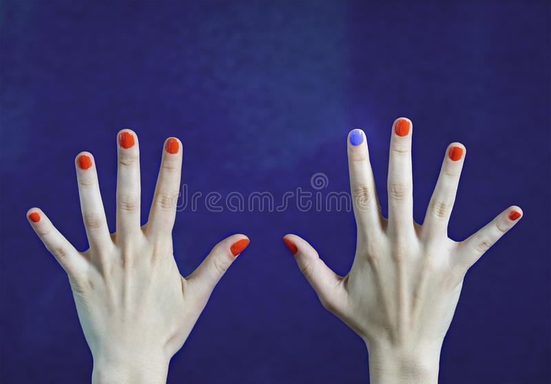 One different nail color in finger in caucasian hands. Red and blue painted fingernails. Stand out from the crowd, originality and creativity concept with blue stock photography