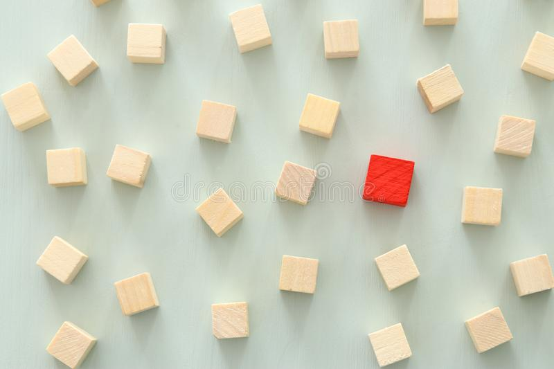 One different red cube block among wooden blocks. Individuality, leadership and uniqueness concept. royalty free stock image