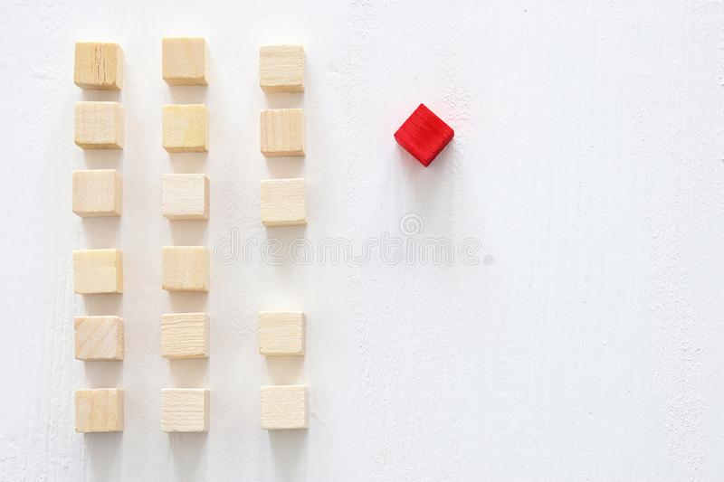 One different red cube block among wooden blocks. Individuality, leadership and uniqueness concept. stock image