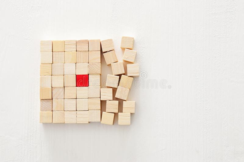 One different red cube block among wooden blocks. Individuality, leadership and uniqueness concept. royalty free stock photography