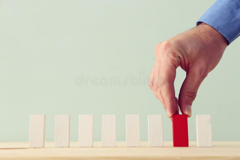 One different red cube block among wooden blocks. Individuality, leadership and uniqueness concept royalty free stock photo