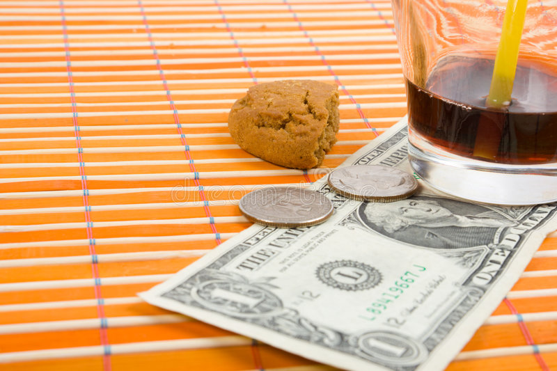 One dollar and 50 cent pay for drink and cookies. On bamboo table-cloth stock image