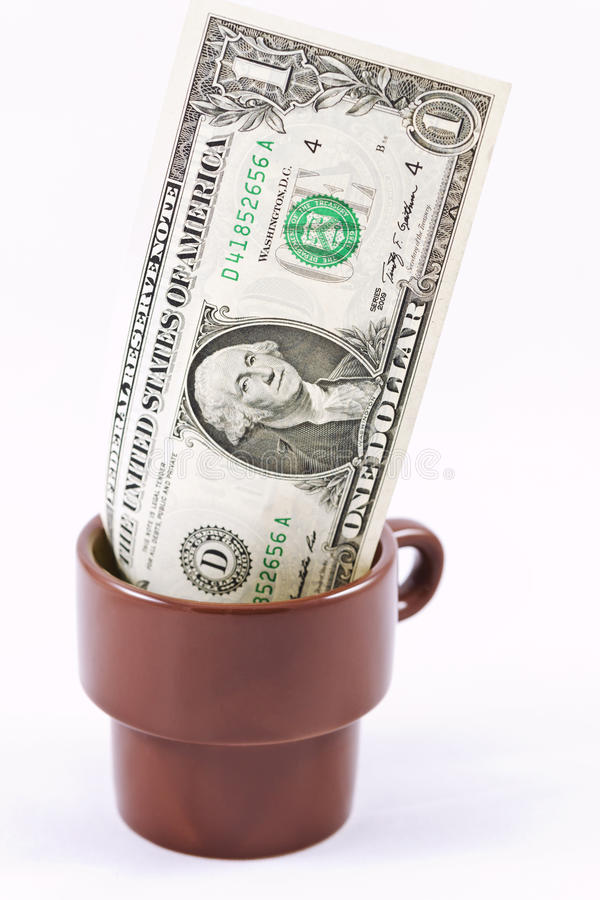One dollar in a coffee Cup left as a tip royalty free stock photography