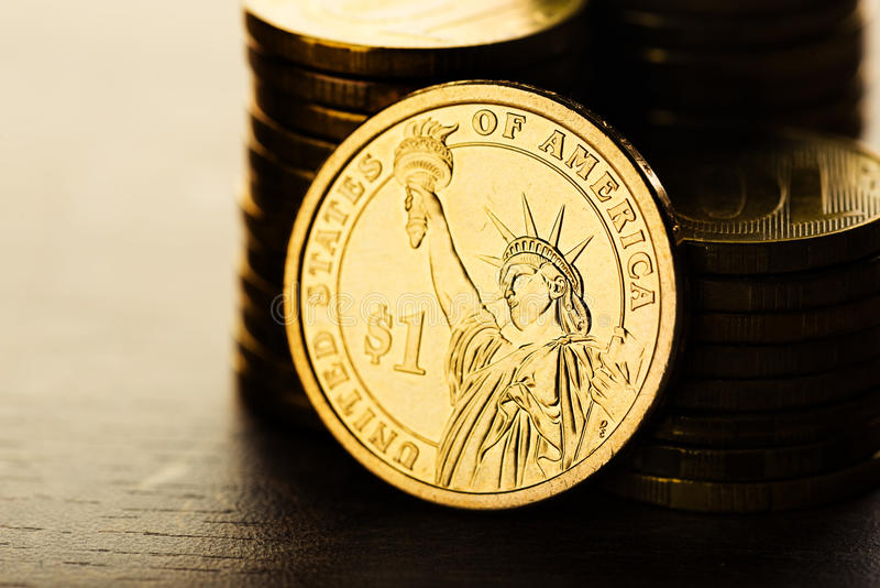 Dollar coin and gold money on the desk. One dollar coin and gold money on the desk stock photo