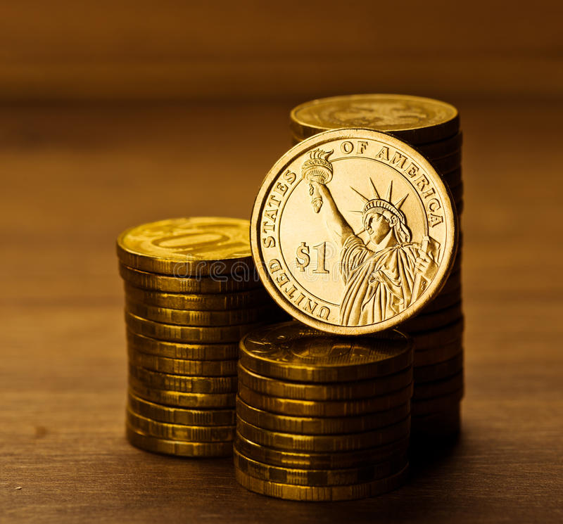 One dollar coin and gold money. On the desk royalty free stock photos