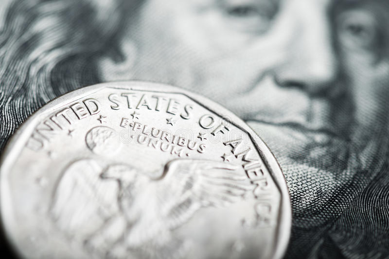 One dollar coin on the one hundred Dollar bill royalty free stock photography