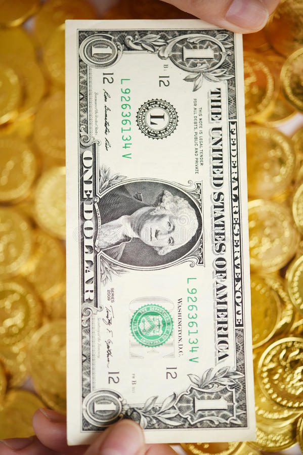 One dollar on hand and gold coins. For background stock images