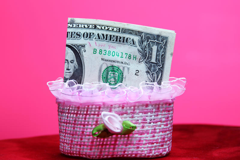 One dollar. Saving one dollar banknote in small box with rose background stock photo