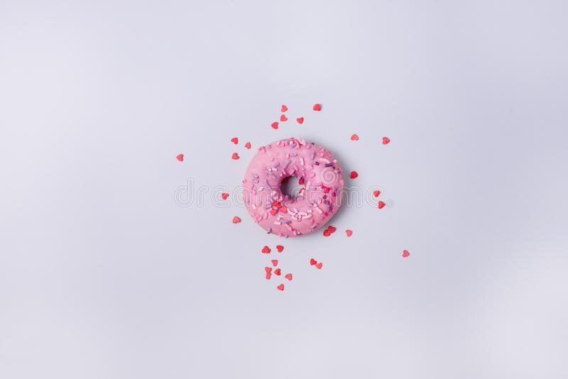 One Donut With Icing on Pastel Pink Blue Background Sweet Tasty Donuts Copy Space Top View Flat Lay.  stock photography