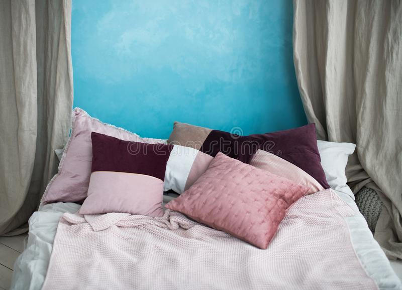 One double bed with pillows stands near a wall of sky-blue, the stock photo