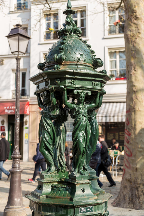 One of the drinking antique Wallace fountains with women group sculpture on in Paris.  royalty free stock images