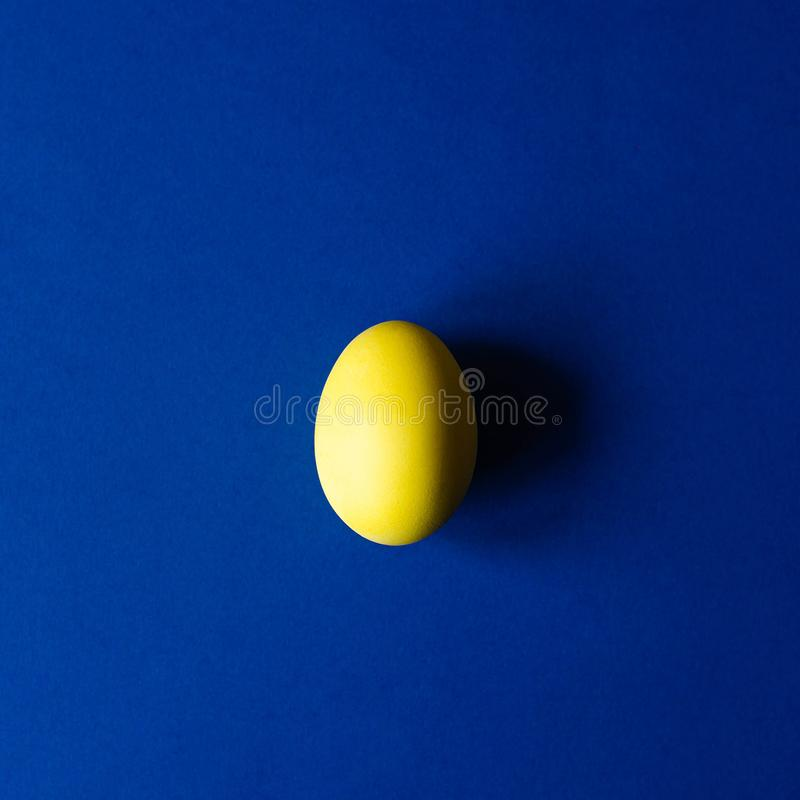 One easter egg of yellow color on a blue background. stock photo