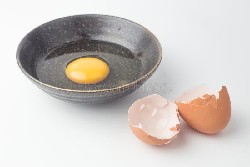 One egg yolks in black bowl and broken egg shells stock photography