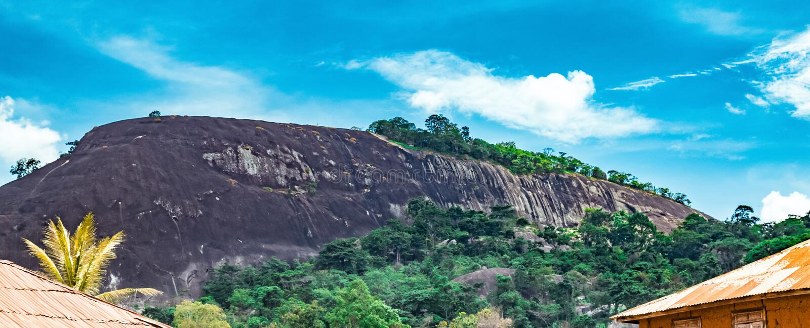 One of the Ekiti Hills in Ikere Ekiti Nigeria. One of the many rock formations in Ekiti State of Nigeria Africa. There is visible housing development at the stock image