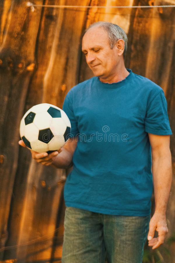An elderly man holding a soccer ball royalty free stock photography