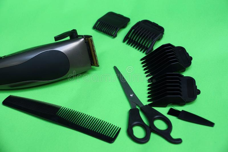 Electric clipper and a set of accessories from scissors, combs and black attachments on a green table stock photos