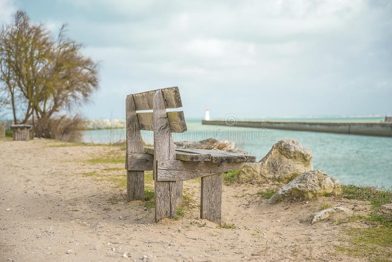 Sea vacations concept. One empty wooden bench in fron tof the berth in the sea royalty free stock photography