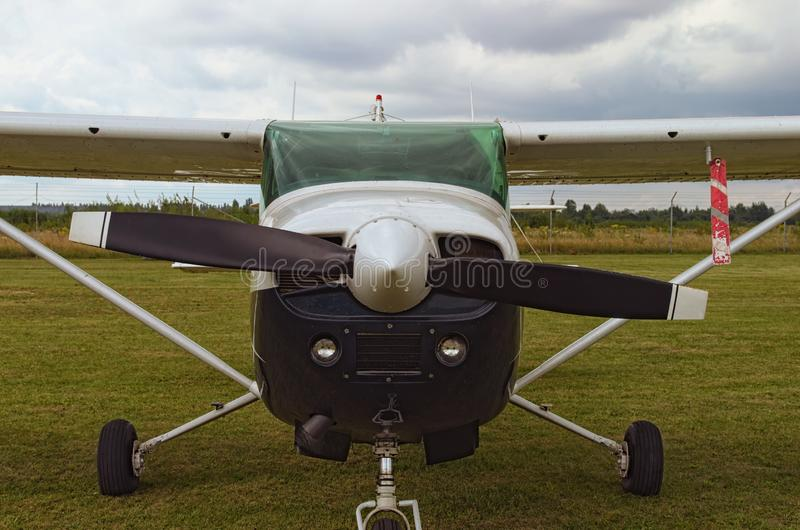 The one engine plane stands on the green grass in a cloudy day. Front view of plain. A small private airfield in Zhytomyr, Ukraine.  stock photography