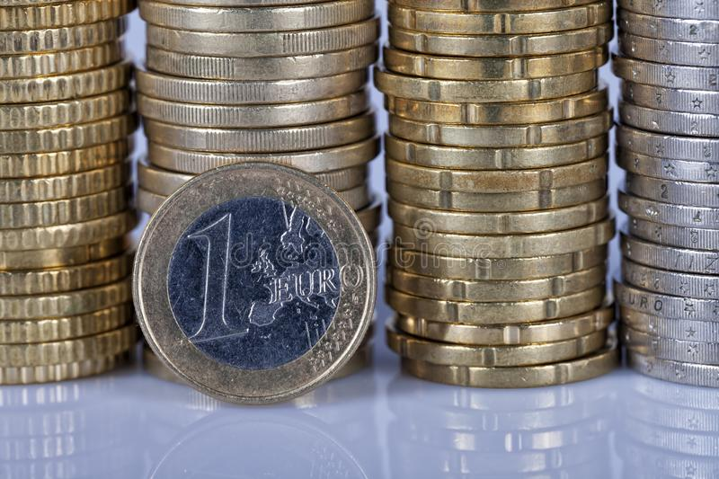 A one euro coin in front of many more coins stacked in columns o stock images