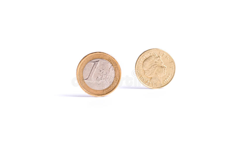 One Euro coin stand in front of the one Pound coin on white back stock images