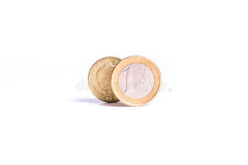 One Euro coin stand in front of the one Pound coin on white back royalty free stock photo
