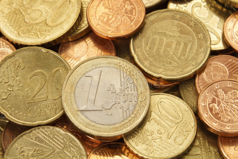 One Euro coin on top of a pile of other Euro coins stock images