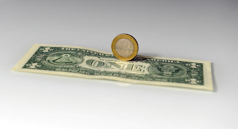 One Euro vs. One Dollar. One Euro placed on one Dollar, on white background royalty free stock photo