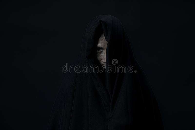 One eye of man in black cover looking to camera on black background royalty free stock photography