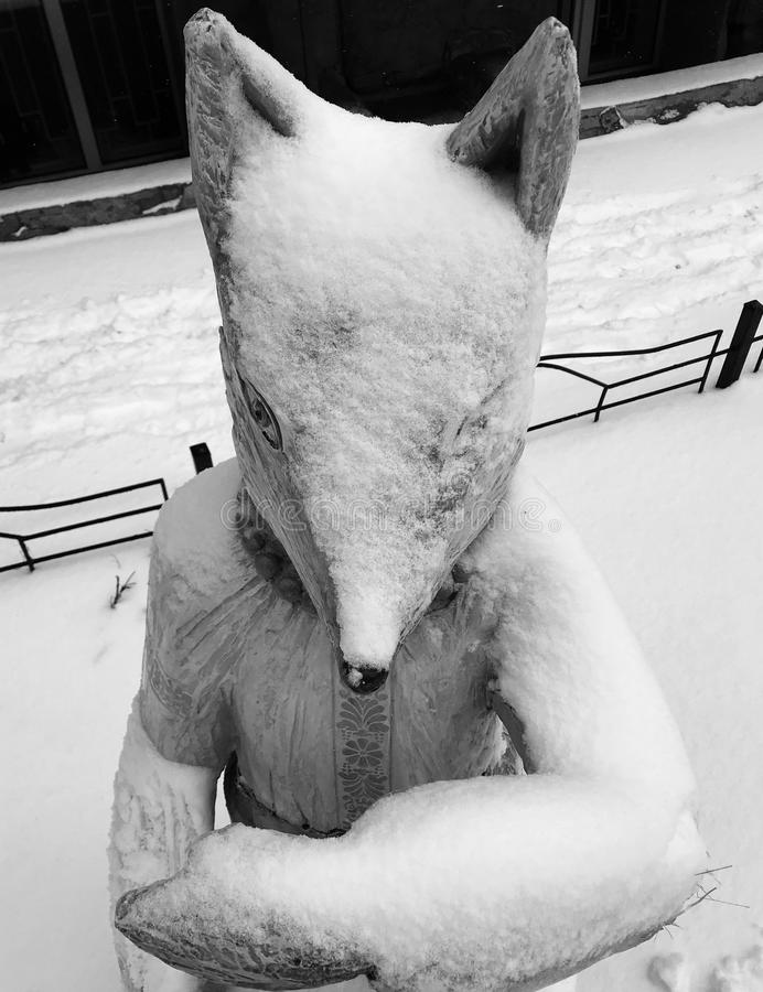 A wooden fox wears a stylish necklace and a coat of white snow in Kyiv - UKRAINE. One eye is open on a trusty and sly fox. The fox wears Ukrainian folk garb stock photography