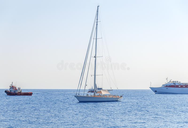 One fancy boat docked at sea and three boat passing by with clean sky stock image