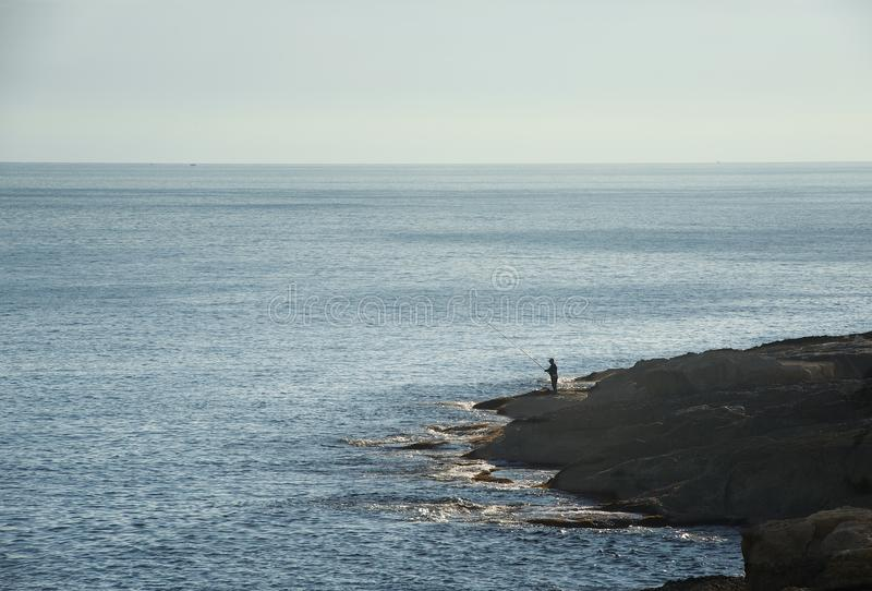 One fisherman on the rock fishing early morning with dusk and dirty sky background, dirty morning light and alone fisherman stock images