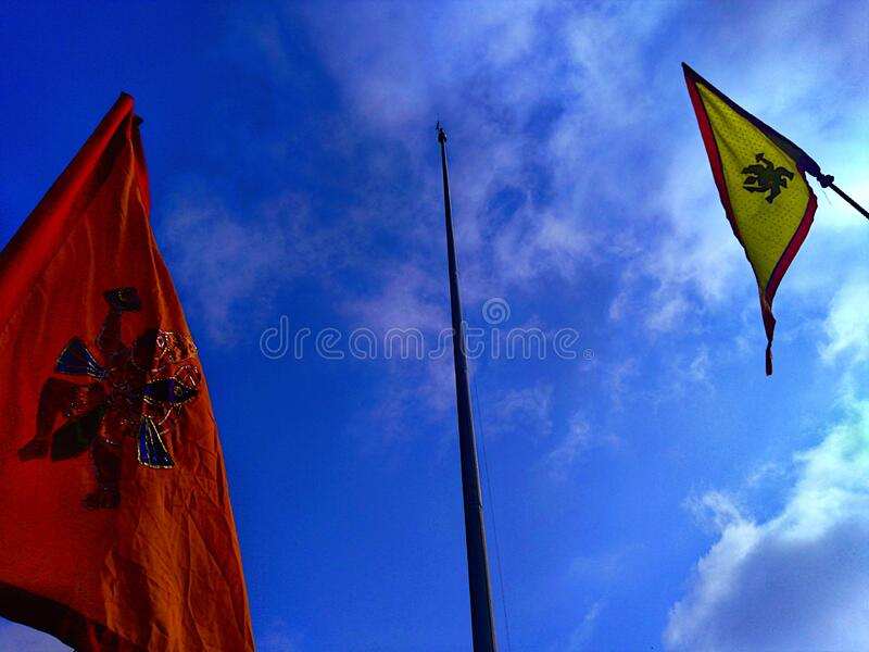 One flagpole with no flag, and two flags of orange and yellow color with the picture of goddess Hanuman. One flagpole with no flag, and two flags of orange and stock images