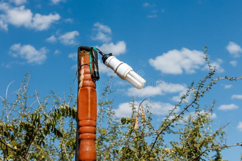 One fluorescent hanging lamp. One fluorescent pendant lamp hanging on a pipe against a blue sky stock photos