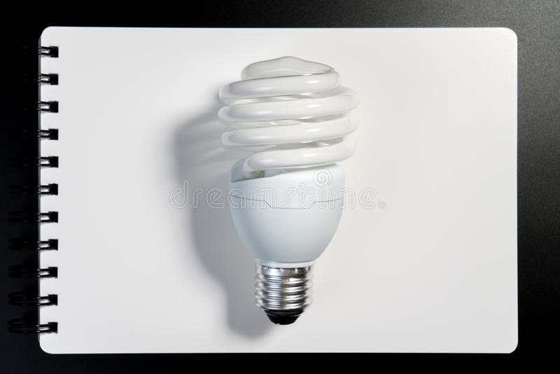 One fluorescent light bulb on white notebook paper on black background for energy saving concept. royalty free stock images