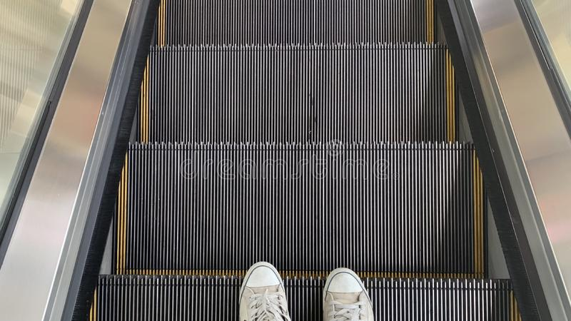 One foot photo while walking down the escalator stock images