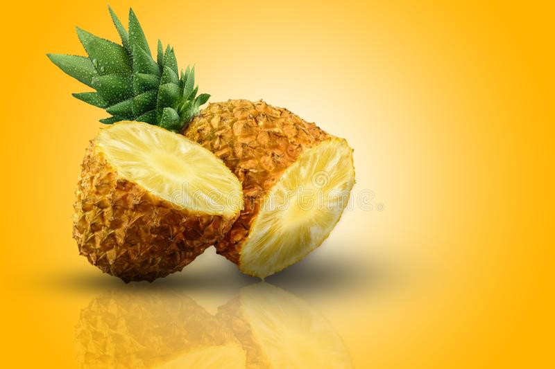 One fresh and very juicy pineapple half in two parts on the orange surface. stock photo