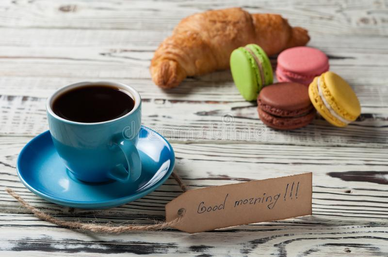 One full blue ceramic cup of fresh black coffee, label with handwritten text good morning near whole baked croissant. And various macaroons on old white rustic stock photo