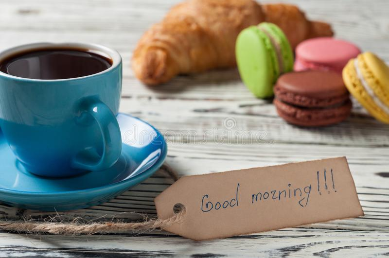 One full blue ceramic cup of fresh black coffee, label with handwritten text good morning near whole baked croissant. And various macaroons on old white rustic royalty free stock photography