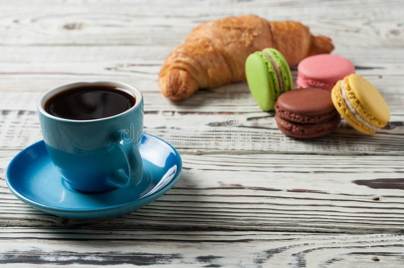 One full blue ceramic cup of fresh black coffee near whole baked croissant and various macaroons. On old white rustic wooden table stock image
