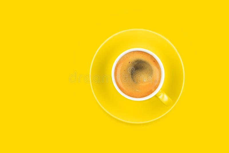 One full espresso coffee cup with saucer on yellow stock photography