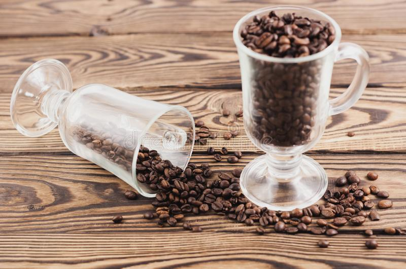 One full of fried coffee beans glass for mulled wine near coffee beans poured out of glass royalty free stock photography
