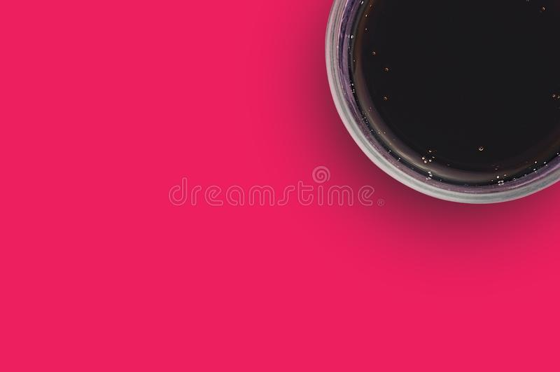 One full glass of aerated cola black color with bubbles on red table in cuisine. Copy space for your text. Top view. Rest concept royalty free stock photo