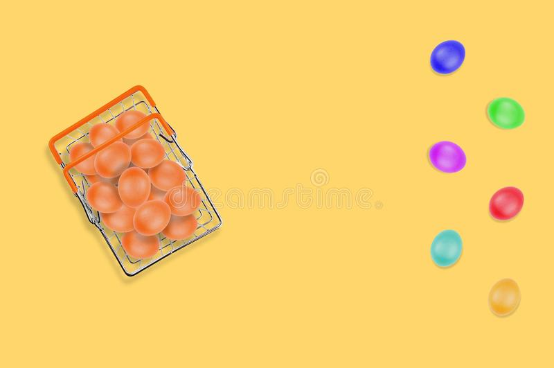 One full glossy metal market basket of fresh raw brown eggs on yellow table on kitchen. Top view. Business concept. Copy space. For your text stock photography