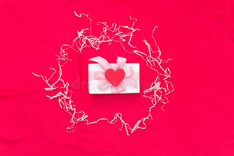 One gift box tied with satin coloured ribbon on a red background a Red heart. stock images