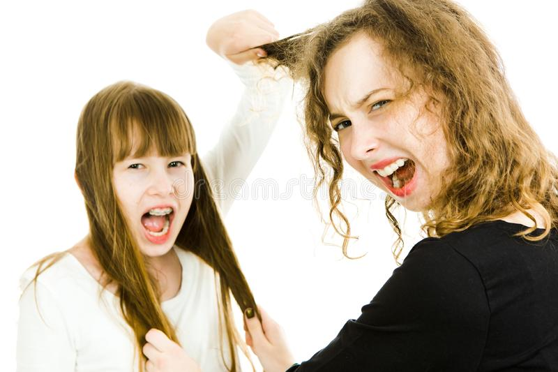 One girl abusing other by pulling her hairs - rivalry royalty free stock photos