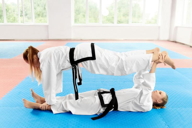 Two young female karate stretching before training in light gym. royalty free stock images