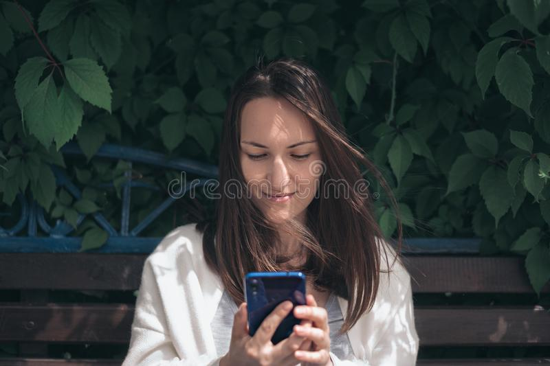 Girl with phone in her hands sitting on bench royalty free stock image
