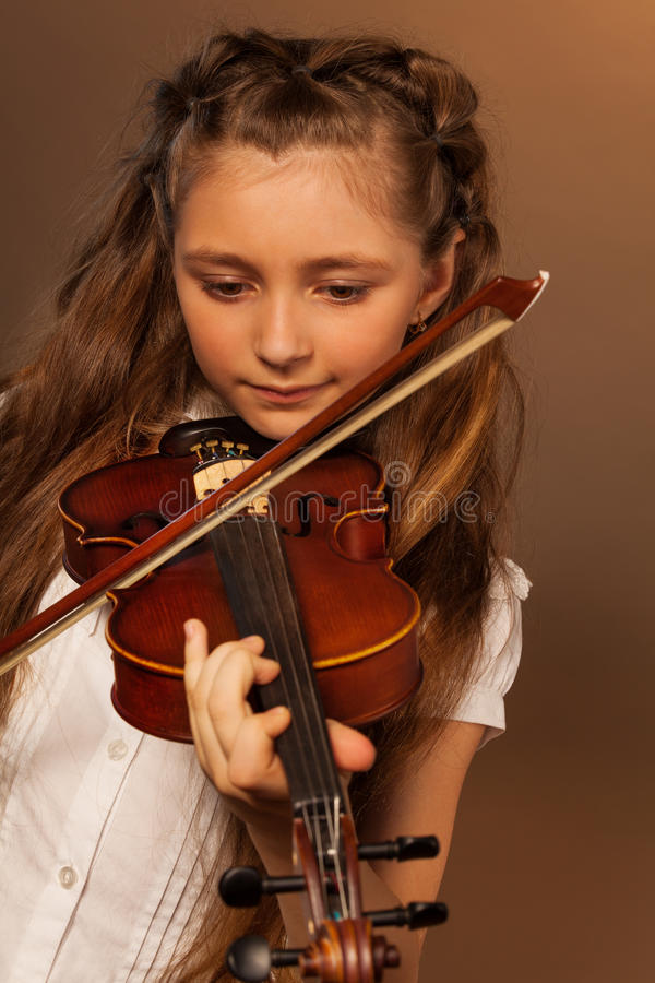 One girl playing the violin on gel background. One girl with long hair holding the fiddlestick and playing on the violin over gel colored dark background royalty free stock photo